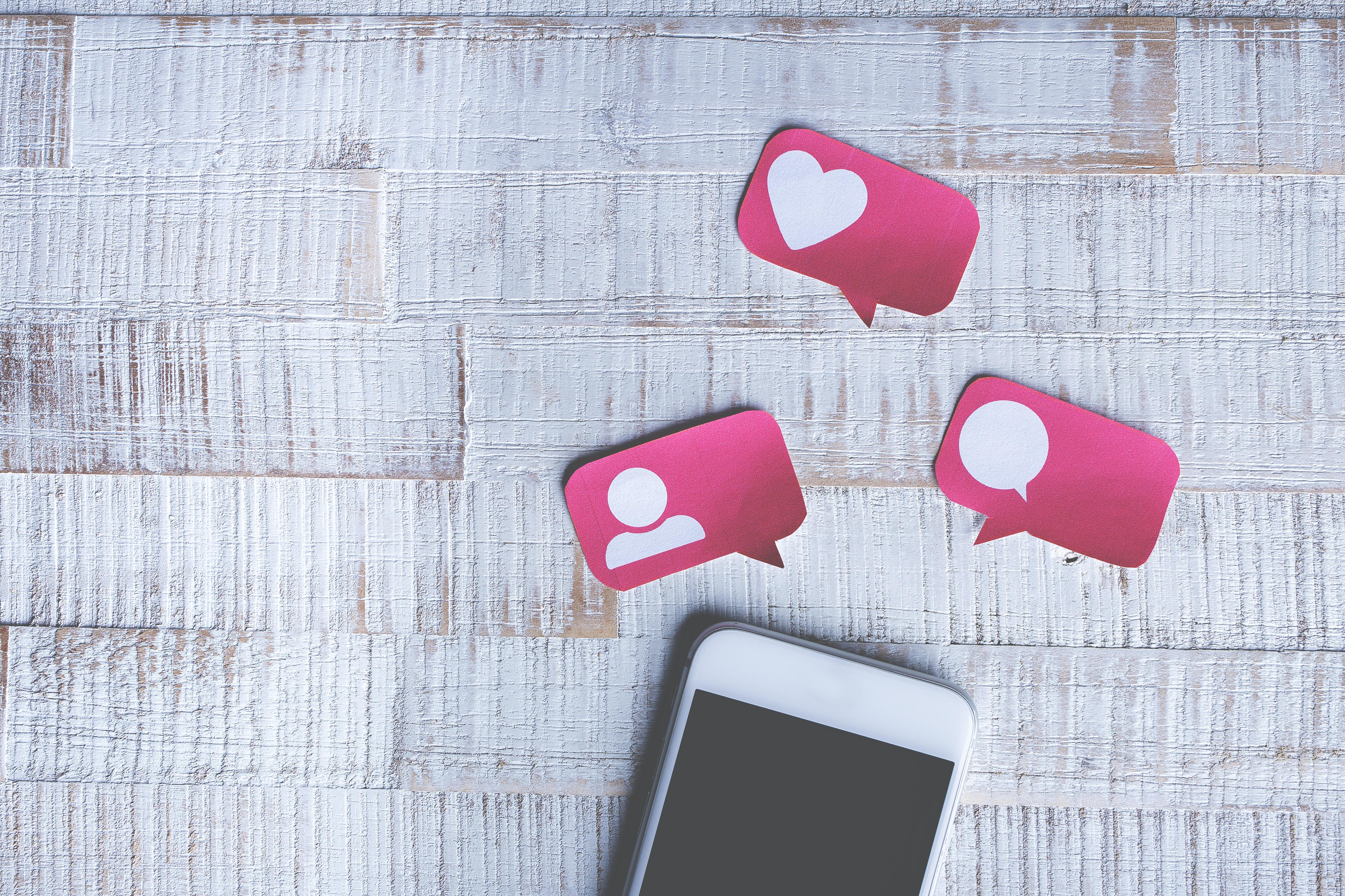 Teléfono en un plato con iconos de papel para me gusta, comentarios y seguidores en Instagram